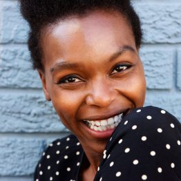 cheerful-african-woman-face-against-gray-wall-PNBJVQE