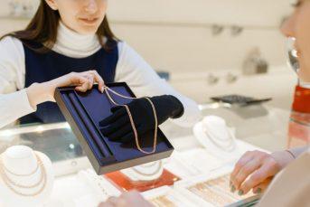 woman-choosing-golden-chain-in-jewelry-store-4TE96XP